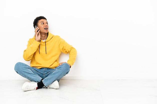 Молодой афроамериканец сидит на полу, изолированном на белом фоне, разговаривает по мобильному телефону