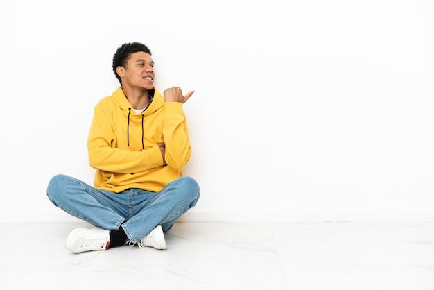 Молодой афроамериканец сидит на полу, изолированном на белом фоне, указывая в сторону, чтобы представить продукт