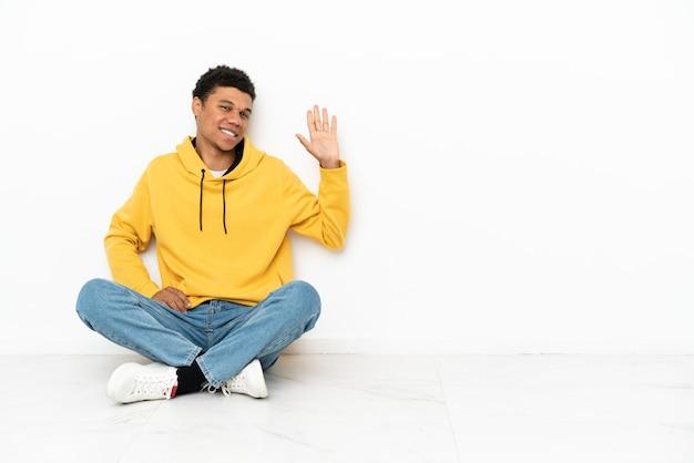 Молодой афро-американский мужчина сидит на полу, изолированном на белом фоне, салютуя рукой с счастливым выражением лица