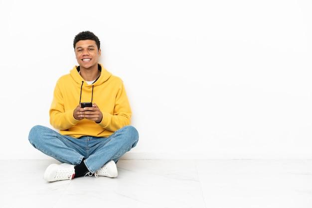 Молодой афро-американский мужчина сидит на полу на белом фоне, отправляя сообщение с мобильного телефона