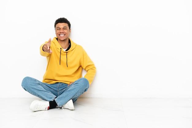 Молодой афроамериканец сидит на полу на белом фоне, пожимая руку для заключения хорошей сделки