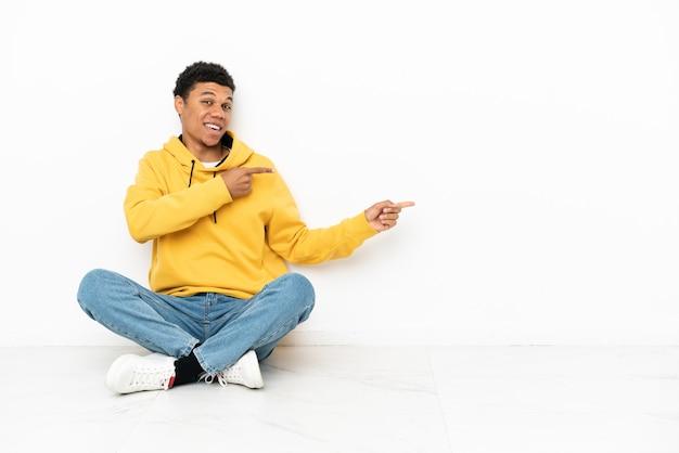 Молодой афро-американский мужчина сидит на полу, изолированном на белом фоне, удивлен и указывая сторону