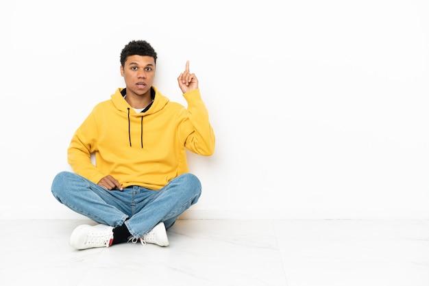 Молодой афроамериканец сидит на полу, изолированном на белом фоне, думает о идее, указывая пальцем вверх
