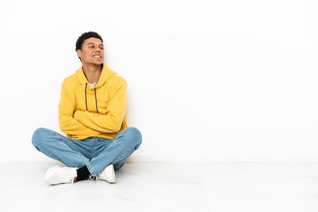 Молодой афро-американский мужчина сидит на полу, изолированном на белом фоне, со скрещенными руками и счастливым