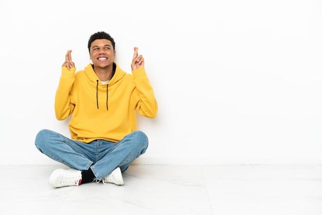 Молодой афро-американский мужчина сидит на полу на белом фоне со скрещенными пальцами