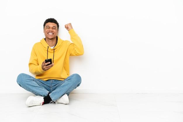 Молодой афро-американский мужчина сидит на полу, изолированном на белом фоне с телефоном в позиции победы