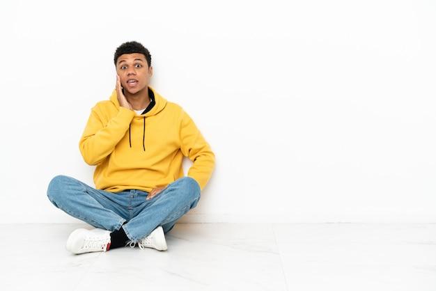 驚きとショックを受けた表情で白い背景で隔離の床に座っている若いアフリカ系アメリカ人の男