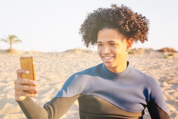 Молодой афроамериканец, сидящий на песке, фотографирует на смартфон