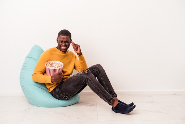 Young african american man sitting on a puff eating popcorn isolated on white background covering ears with hands.