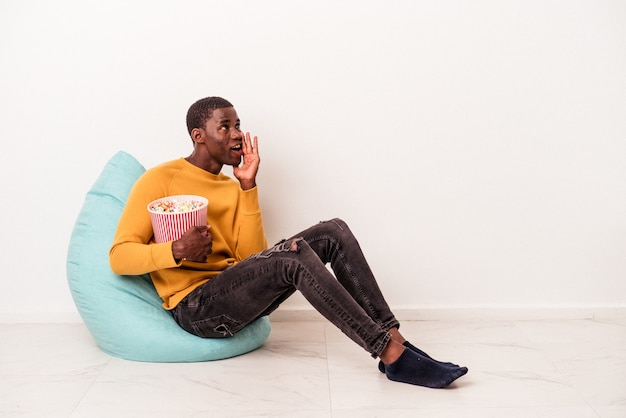 Young african american man sitting on a puff eating popcorn isolated on white background is saying a secret hot braking news and looking aside