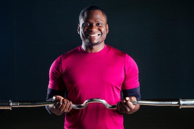 젊은 아프리카계 미국인 스포츠맨 쪼그리고 앉는 스포츠맨 아령 티셔츠 스포츠 유니폼 스포츠 착용 검은 배경 스튜디오 체육관