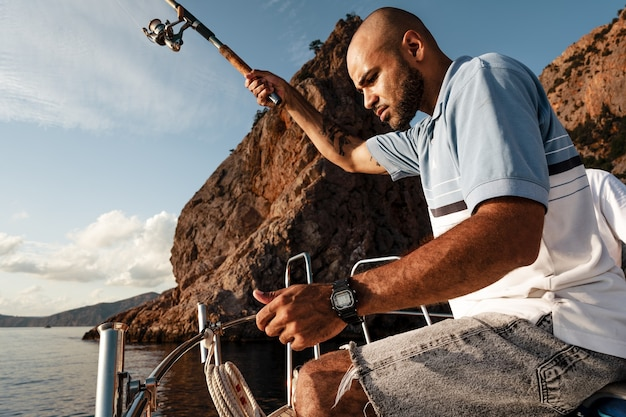 일몰에 넓은 바다에서 낚시를 하는 요트에 낚싯대를 들고 서 있는 젊은 아프리카계 미국인 남자