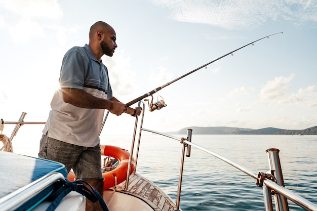 Young african american man standing with fishing rod on a sailboat fishing in open sea on sunset