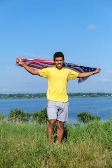 미국 국기와 함께 뻗은 팔을 들고 서 있는 젊은 아프리카계 미국인 남자