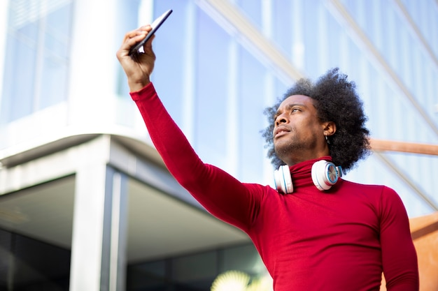 Young african american man taking a picture of himself with a smart phone. he is outdoors next to a modern building. space for text.