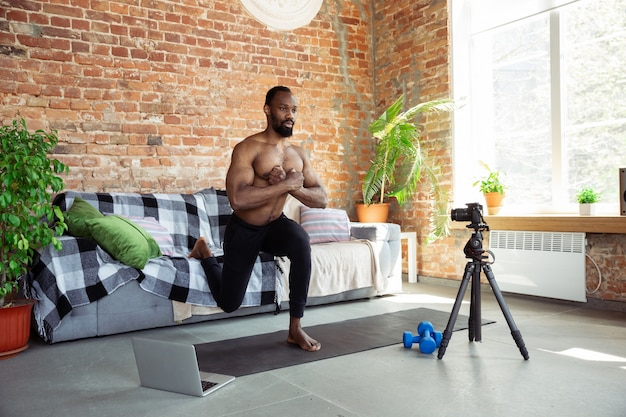 Young african-american man teaching at home online courses of fitness, aerobic, sporty lifestyle during quarantine, reording on camera, streaming