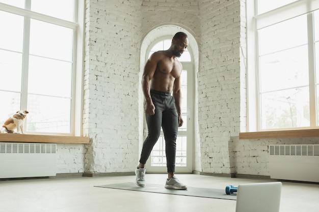 Молодой афро-американский мужчина тренируется дома во время карантина