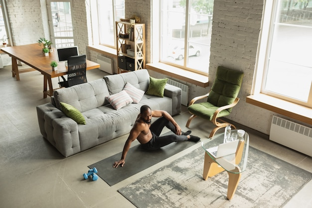 Young african-american man training at home , doing exercises of fitness, aerobic.