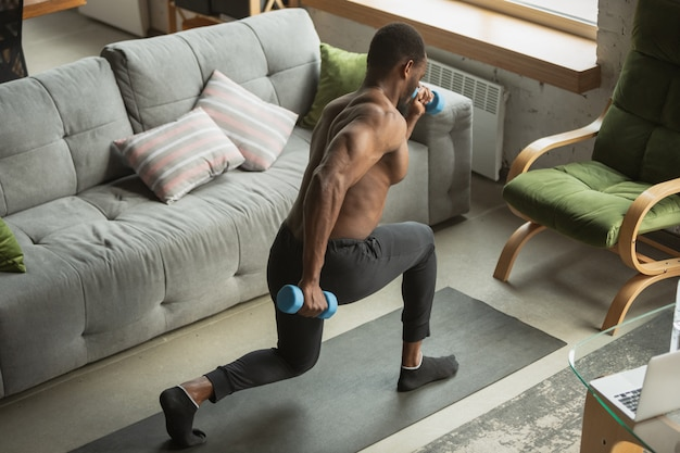 Young african-american man training at home , doing exercises of fitness, aerobic