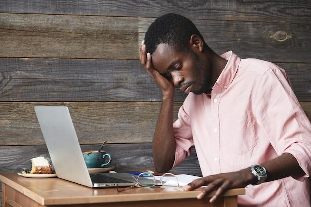Giovane uomo afro-americano utilizzando laptop