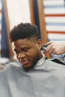 Young african-american man visiting barbershop