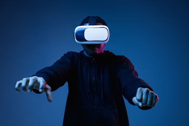 Young african-american man in vr-glasses in neon on blue background. male portrait