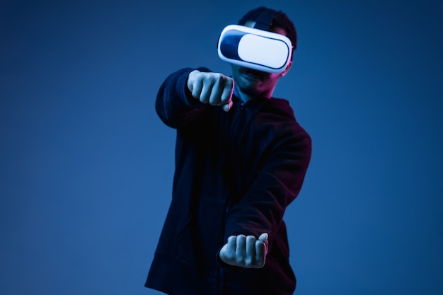 Young african-american man in vr-glasses in neon on blue