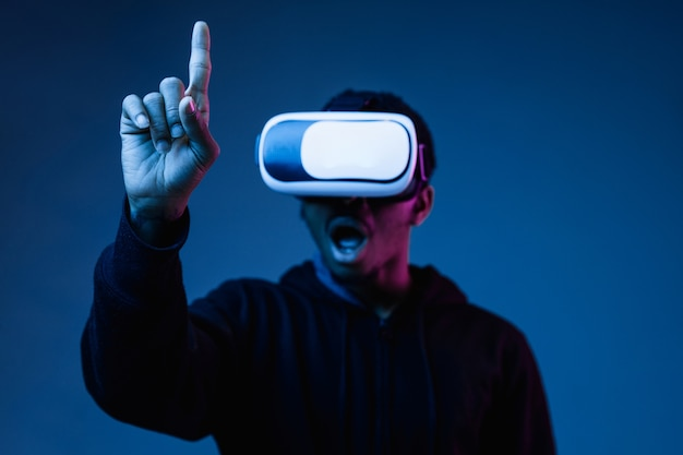 Young african-american man in vr-glasses in neon light on blue
