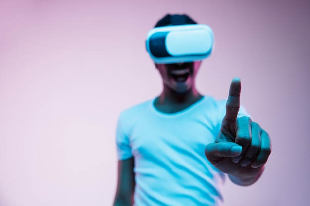 Young african-american man in vr-glasses in neon light on gradient background. male portrait