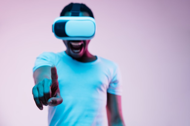 Young african-american man in vr-glasses in neon light on gradient