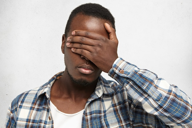 Молодой афроамериканец в клетчатой рубашке поверх белой футболки, закрывая лицо рукой