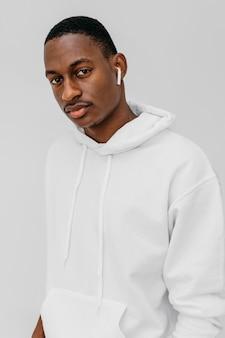 Giovane uomo afroamericano che indossa una felpa con cappuccio bianca e un paio di auricolari