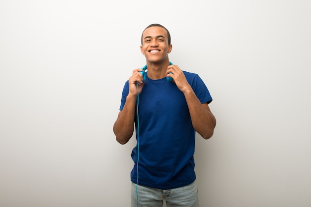 Young african american man on white wall with headphones