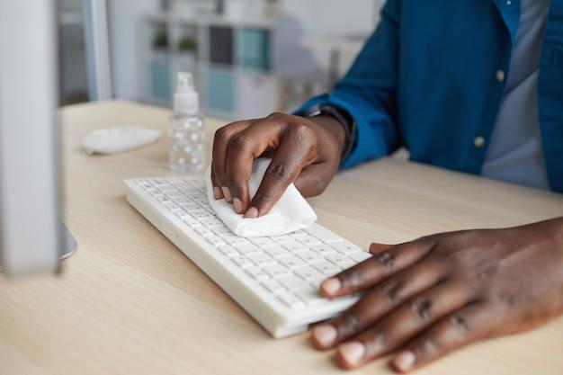 Молодой афроамериканец протирает клавиатуру дезинфицирующими салфетками, работая за столом в офисе после пандемии