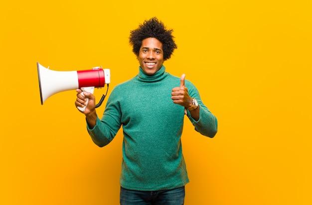 オレンジ色の背景に対してメガホンを持つ若いアフリカ系アメリカ人