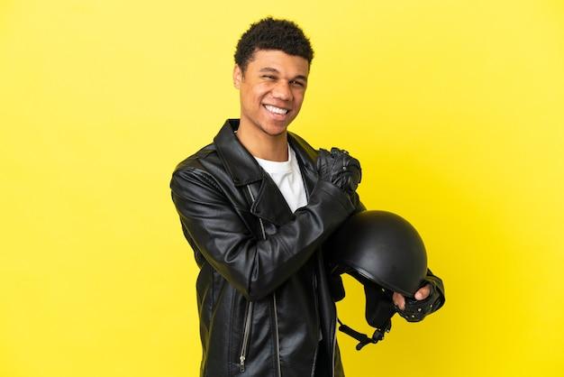 勝利を祝う黄色の背景に分離されたオートバイのヘルメットを持つ若いアフリカ系アメリカ人の男