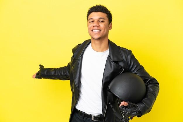 Молодой афроамериканец в мотоциклетном шлеме изолирован на желтом фоне, протягивая руки в сторону, приглашая приехать