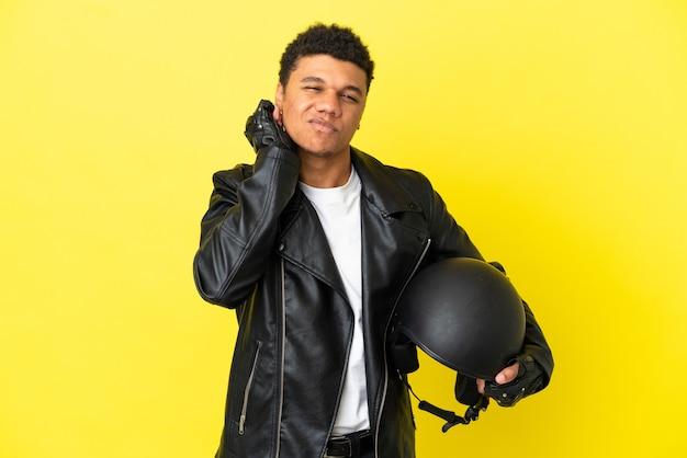 Молодой афроамериканец в мотоциклетном шлеме на желтом фоне разочарован и закрывает уши