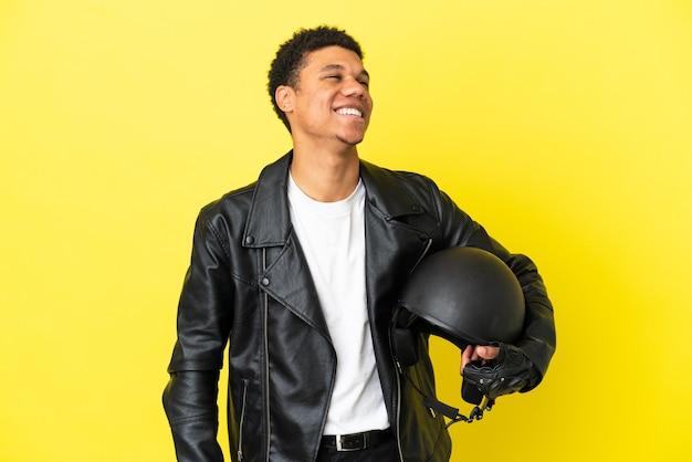 Молодой афро-американский мужчина в мотоциклетном шлеме на желтом фоне смеется