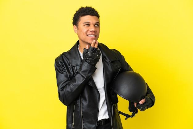 Молодой афро-американский мужчина в мотоциклетном шлеме изолирован на желтом фоне, глядя вверх, улыбаясь