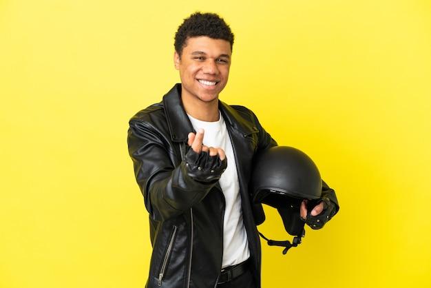 Молодой афроамериканец с мотоциклетным шлемом, изолированным на желтом фоне, делая денежный жест