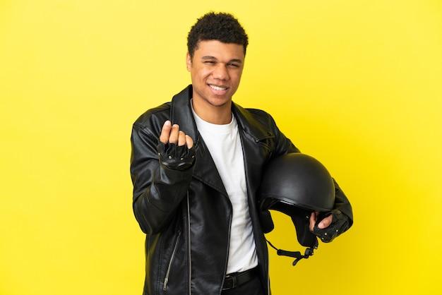 Молодой афро-американский мужчина с мотоциклетным шлемом, изолированным на желтом фоне, делая денежный жест