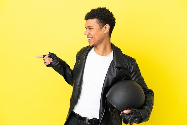 노란색 배경에 격리된 오토바이 헬멧을 쓴 젊은 아프리카계 미국인 남성이 손가락을 옆으로 가리키고 제품을 제시합니다.