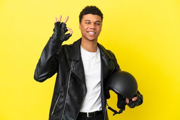 노란색 배경에 오토바이 헬멧을 쓴 젊은 흑인 남성이 손가락으로 확인 표시를 하고 있다