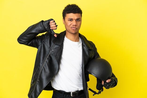 Молодой афроамериканец в мотоциклетном шлеме на желтом фоне показывает большой палец вниз с негативным выражением лица