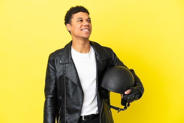 노란색 배경에 오토바이 헬멧을 쓴 젊은 아프리카계 미국인 남자가 올려다보며 아이디어를 생각하고 있다