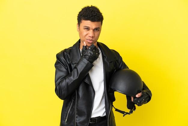 Молодой афро-американский мужчина с мотоциклетным шлемом, изолированным на желтом фоне, думает