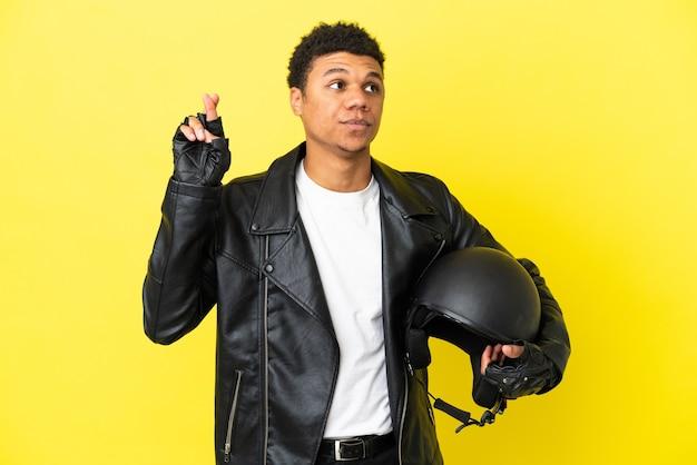 Молодой афроамериканец в мотоциклетном шлеме изолирован на желтом фоне со скрещенными пальцами и желает всего наилучшего