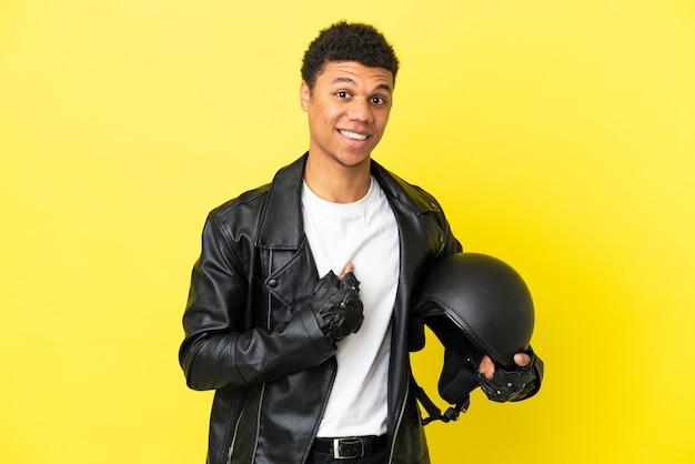 驚きの表情で黄色の背景に分離されたオートバイのヘルメットを持つ若いアフリカ系アメリカ人の男