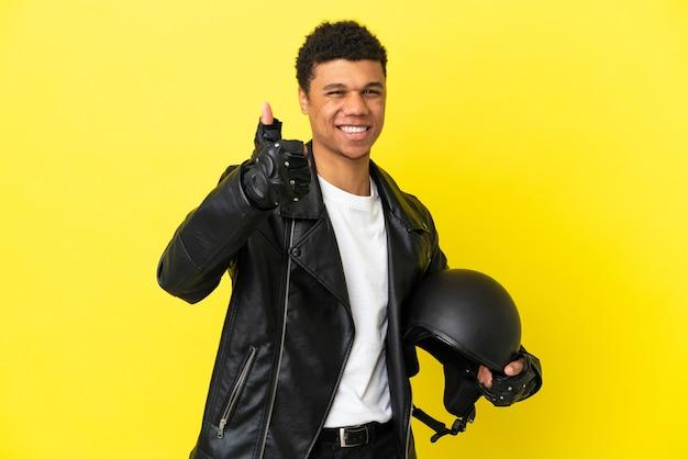 Молодой афроамериканец в мотоциклетном шлеме изолирован на желтом фоне с большими пальцами руки вверх, потому что произошло что-то хорошее